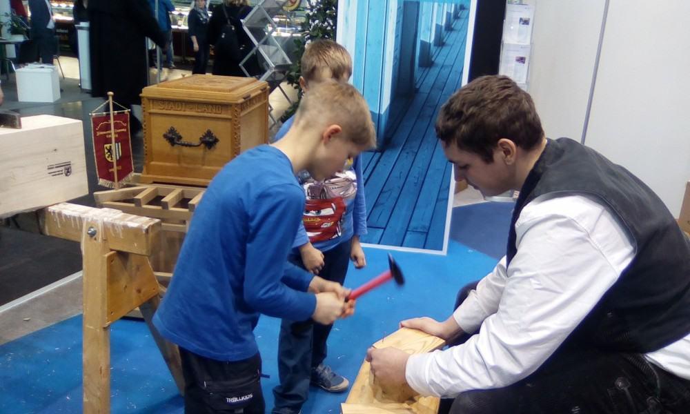 Kinder bauen am Stand der Zimmerer Innung Leipzig Nistkästen.