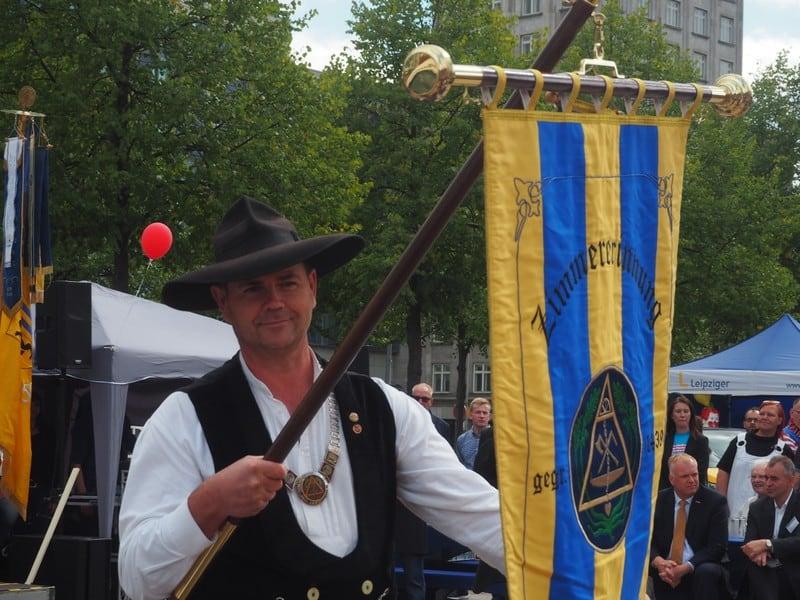 Innungsobermeister Haiko Schult präsentiert die neue Innungsfahne beim Tag des Handwerks auf dem Augustusplatz in Leipzig.